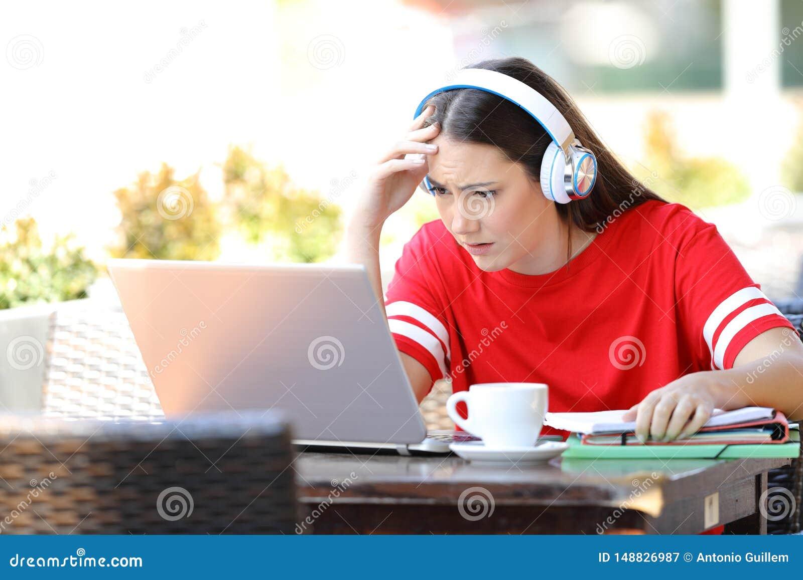 Apprentissage en ligne inqui?t? d ?tudiant avec un ordinateur portable dans un caf?
