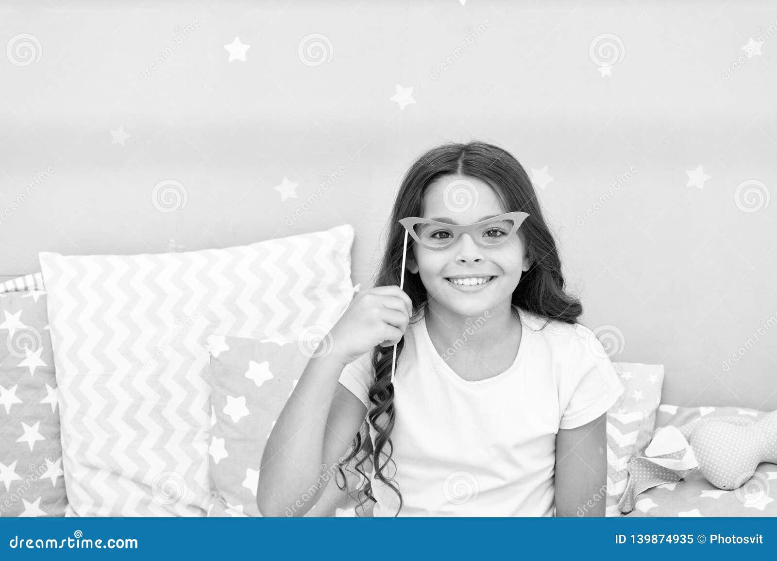 Appui verticaux de cabine de photo de soirée pyjamas La pose gaie de fille d enfant avec de rétros lunettes roses font la fête l