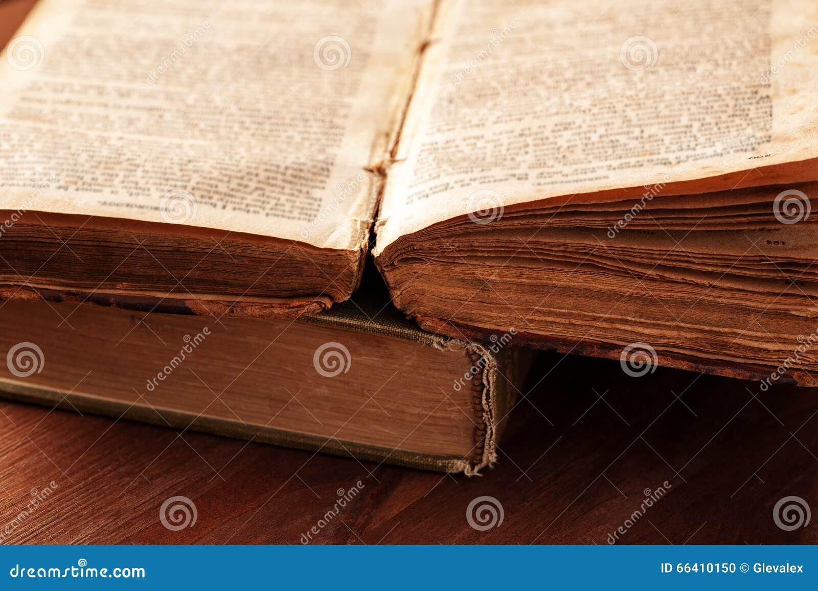 Apra il vecchio libro con il primo piano sfilacciato delle pagine