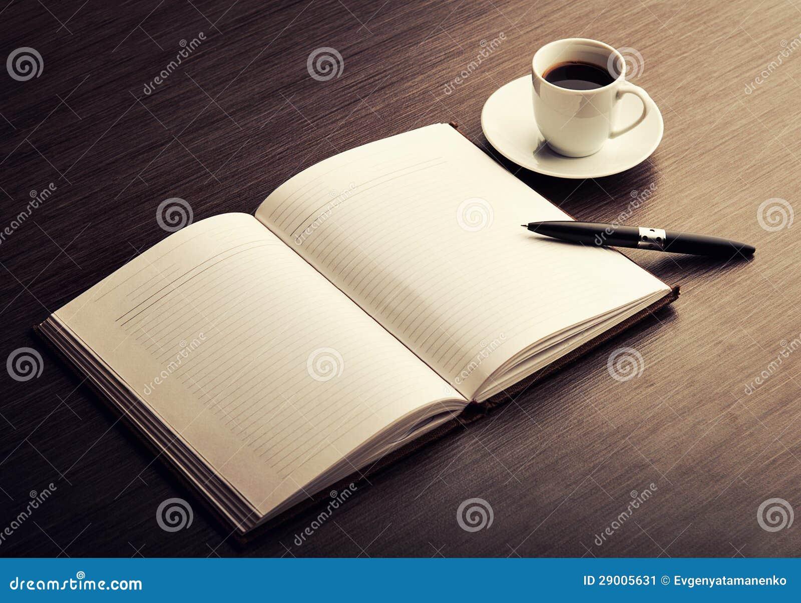 Apra un taccuino, una penna e un caffè bianchi in bianco sullo scrittorio