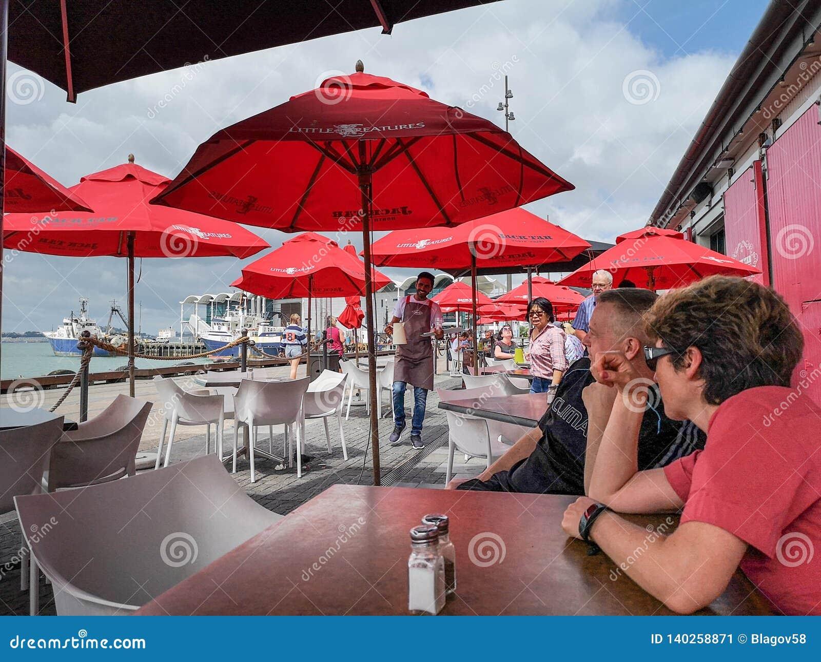 Apreciando a conversação no café da margem de Auckland Bacia do porto do viaduto