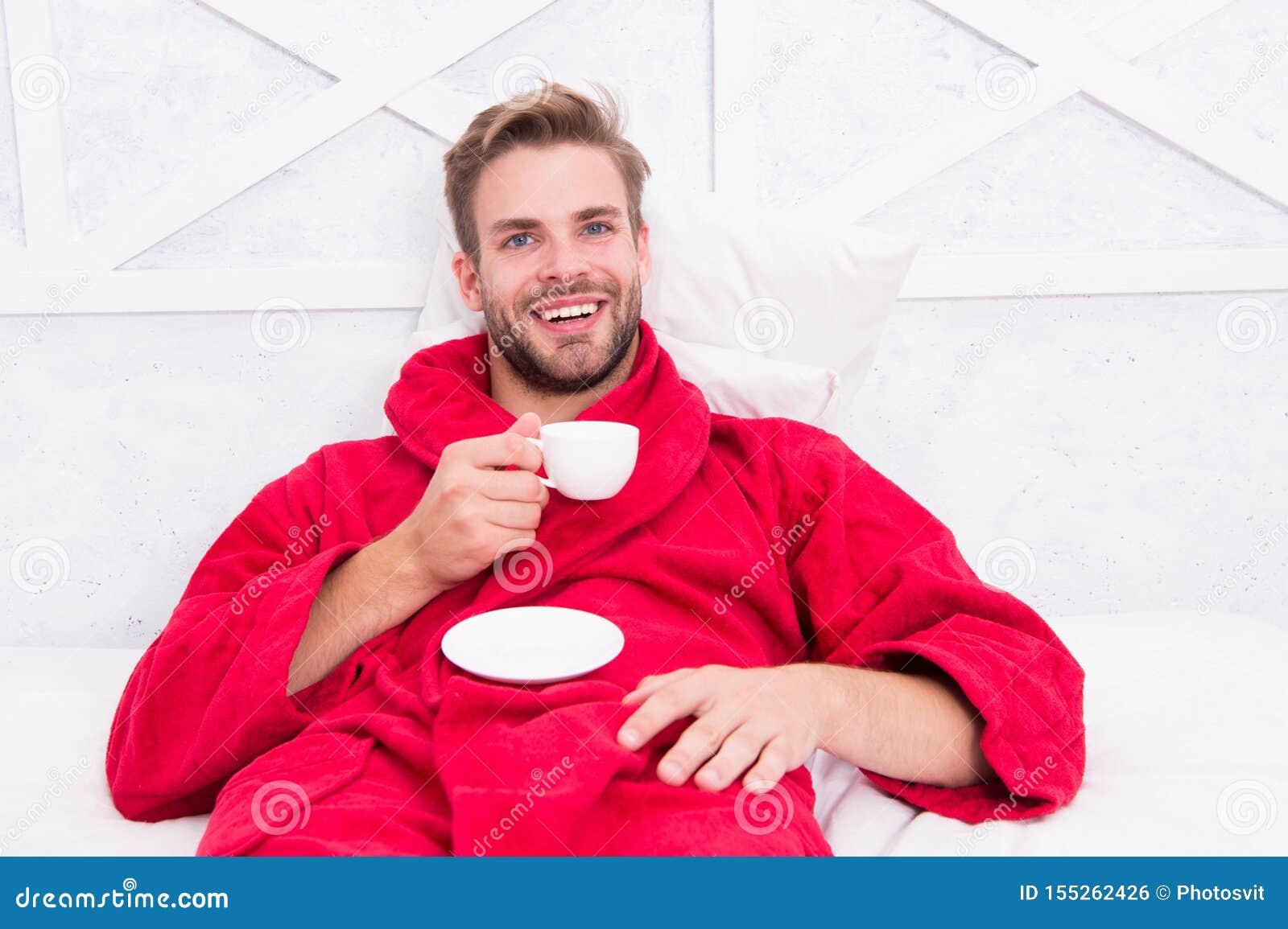 Aprecie o caf? da manh? Manh? feliz Café considerável da manhã da bebida do homem homem farpado feliz na cama Bom modo gourmet