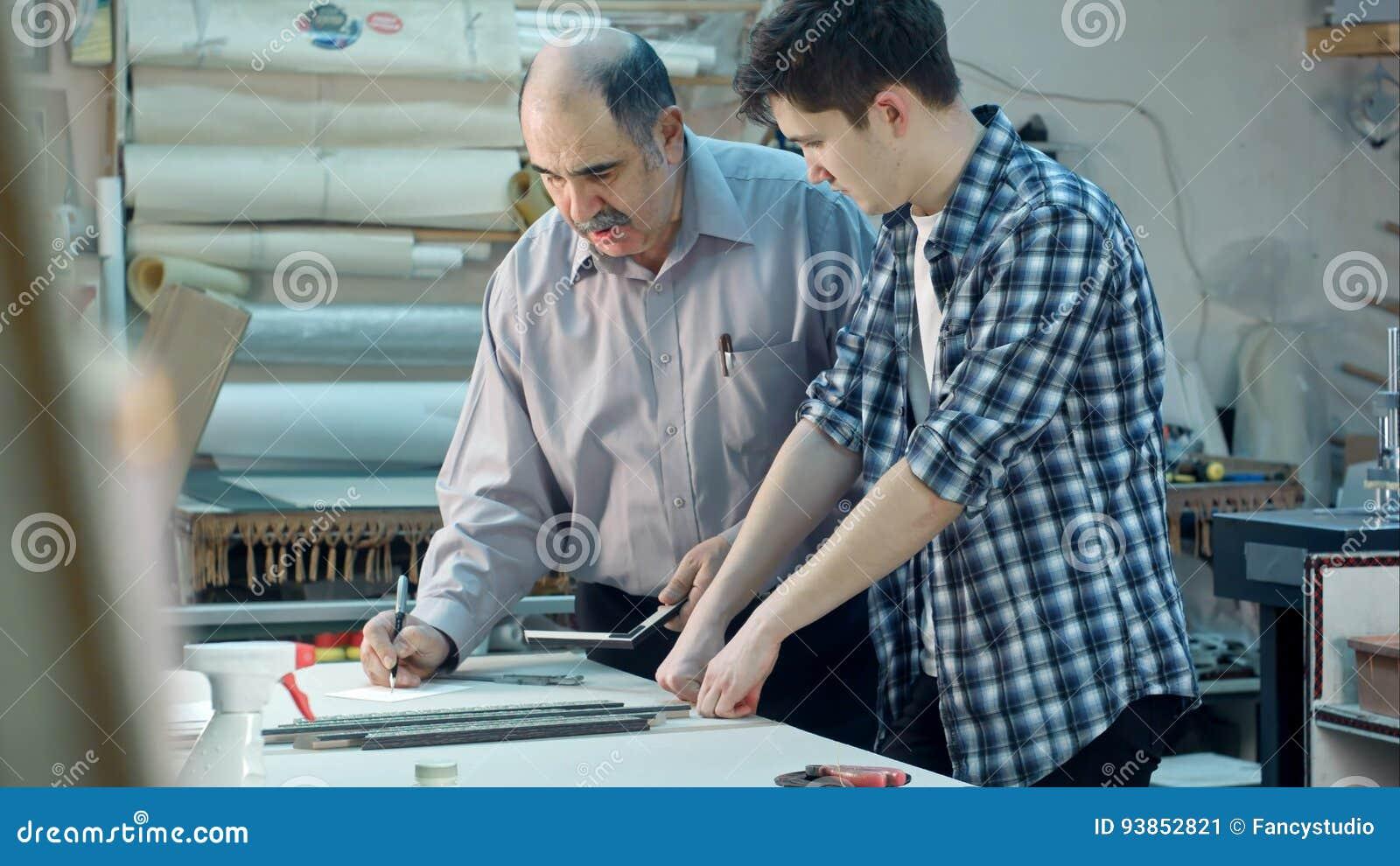 Aprendiz Joven Que Estudia Cómo Construir Un Marco, Trabajador Mayor ...
