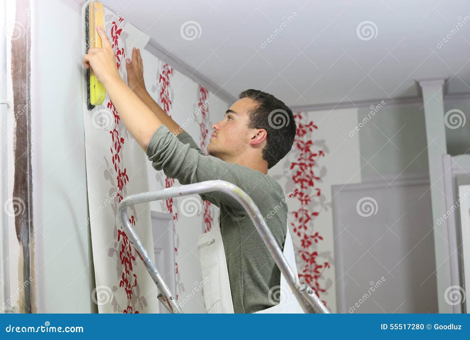 Aprendiz joven que pone el papel pintado
