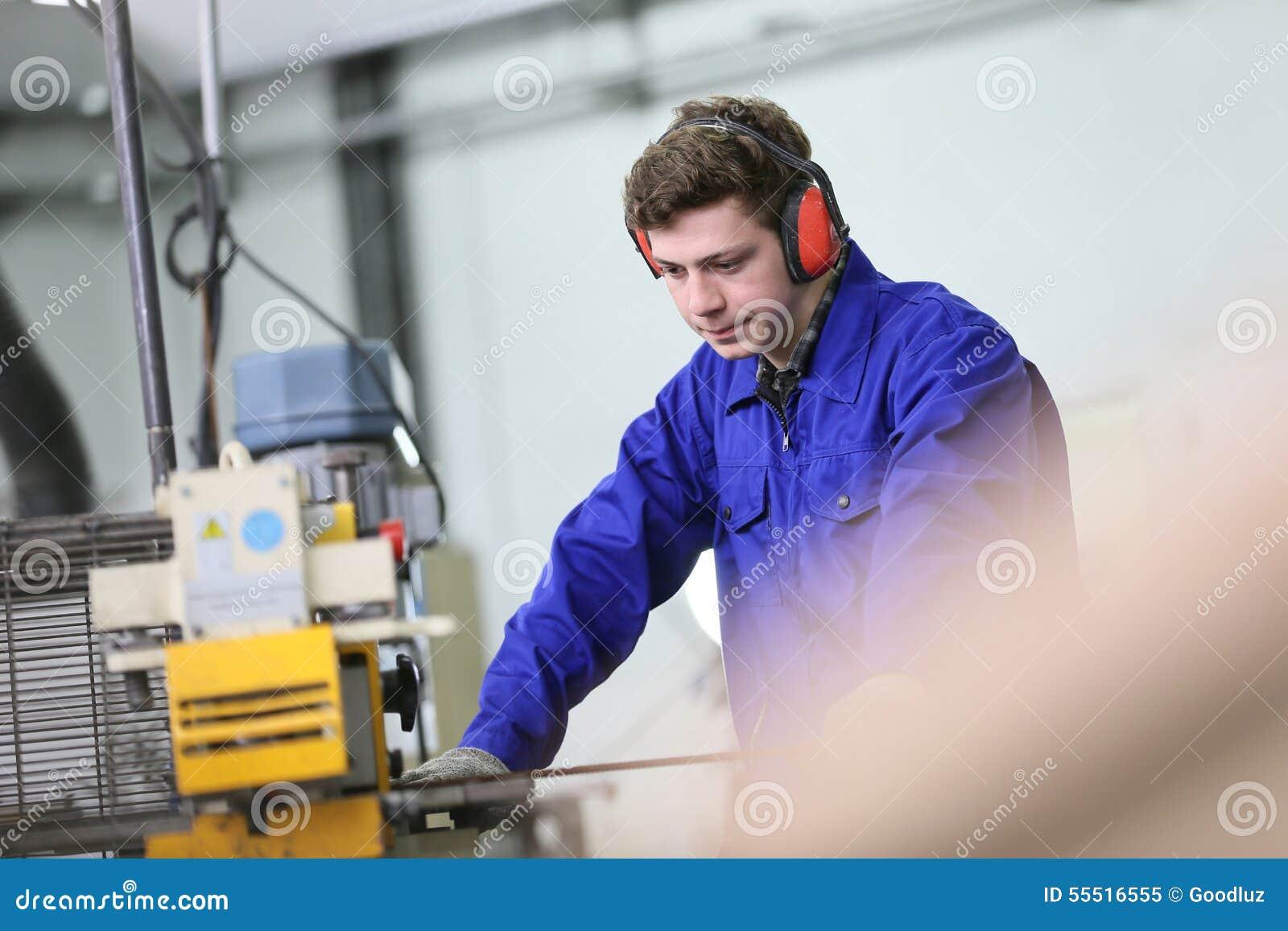 Aprendiz joven que trabaja en taller de la metalurgia