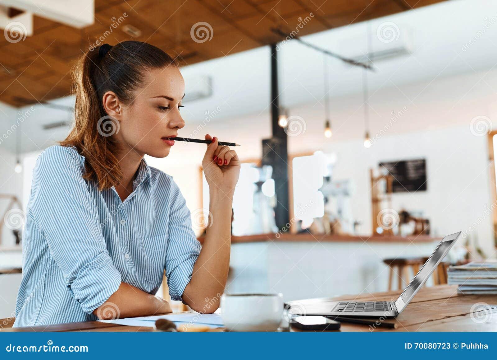 Aprendizagem, estudando Mulher que usa o laptop no café, trabalhando