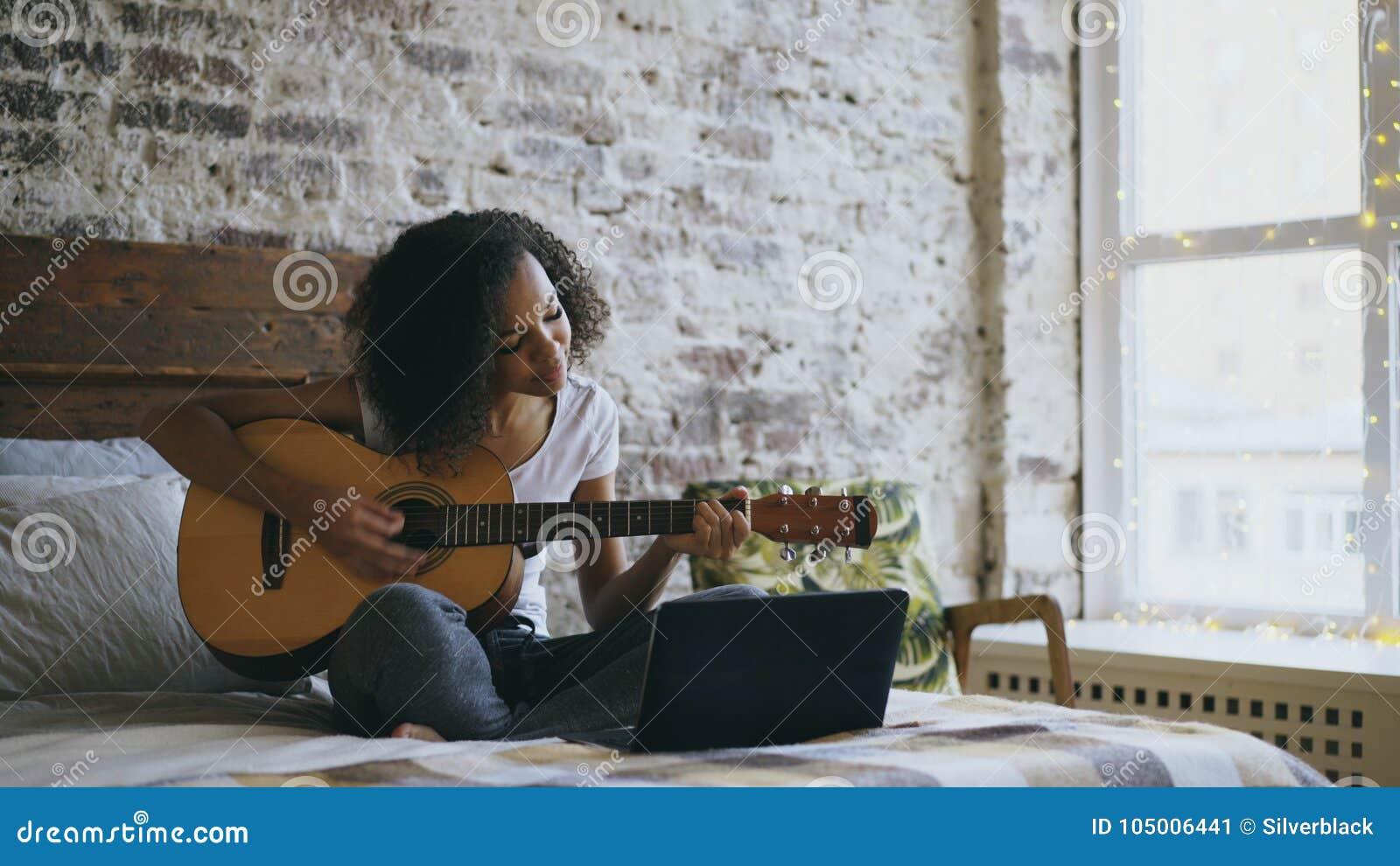 Aprendizaje concentraing de la muchacha afroamericana rizada del adolescente tocar la guitarra usando el ordenador portátil que s
