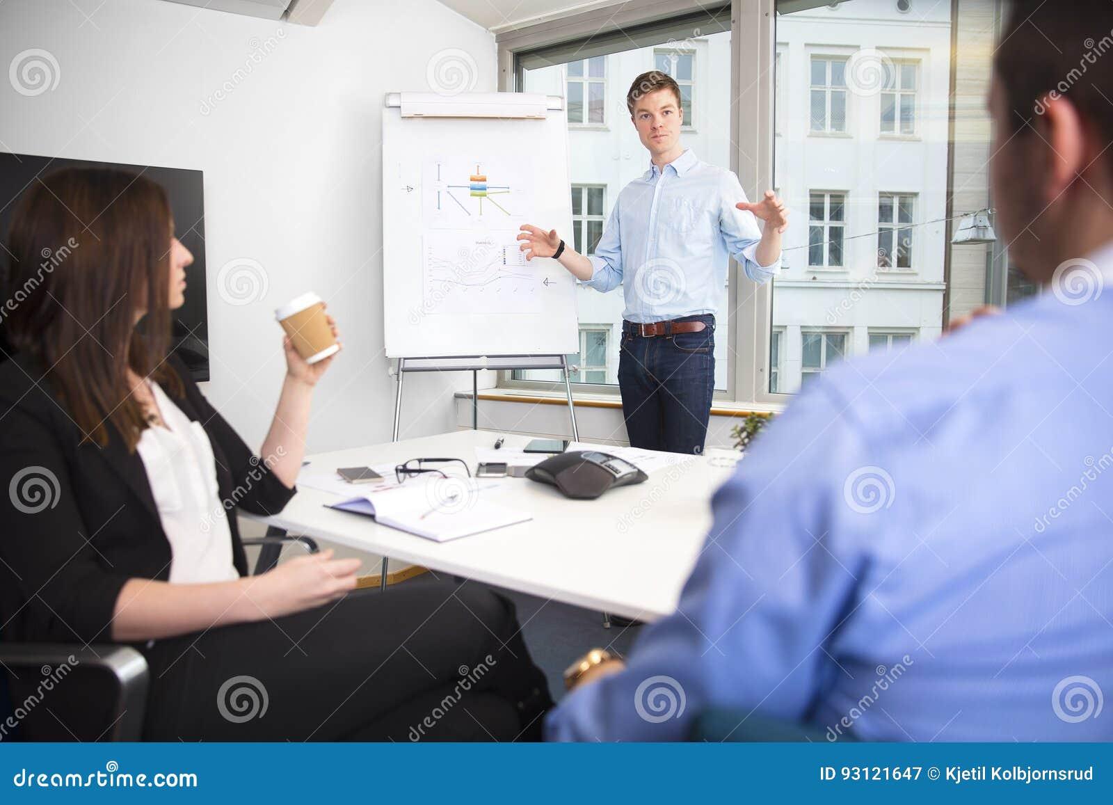 Apresentação de Gesturing While Giving do homem de negócios aos colegas