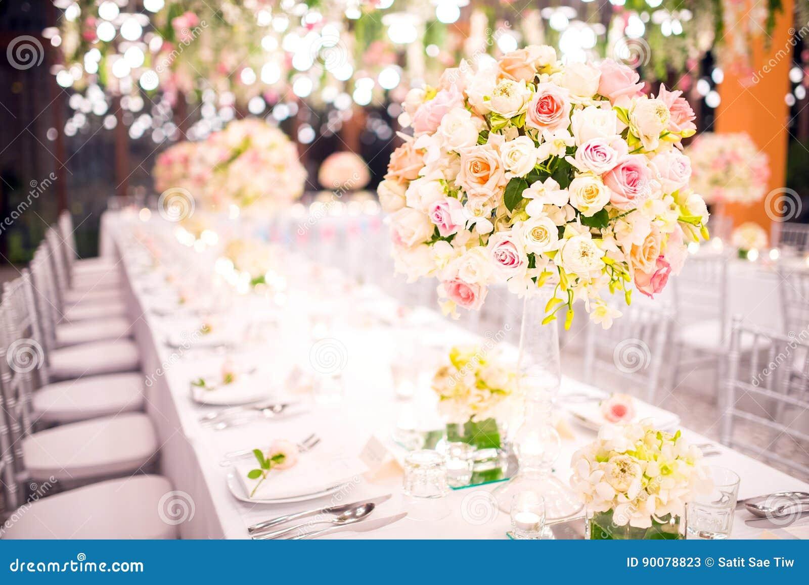 Apresente o ajuste em um casamento luxuoso e em umas flores bonitas