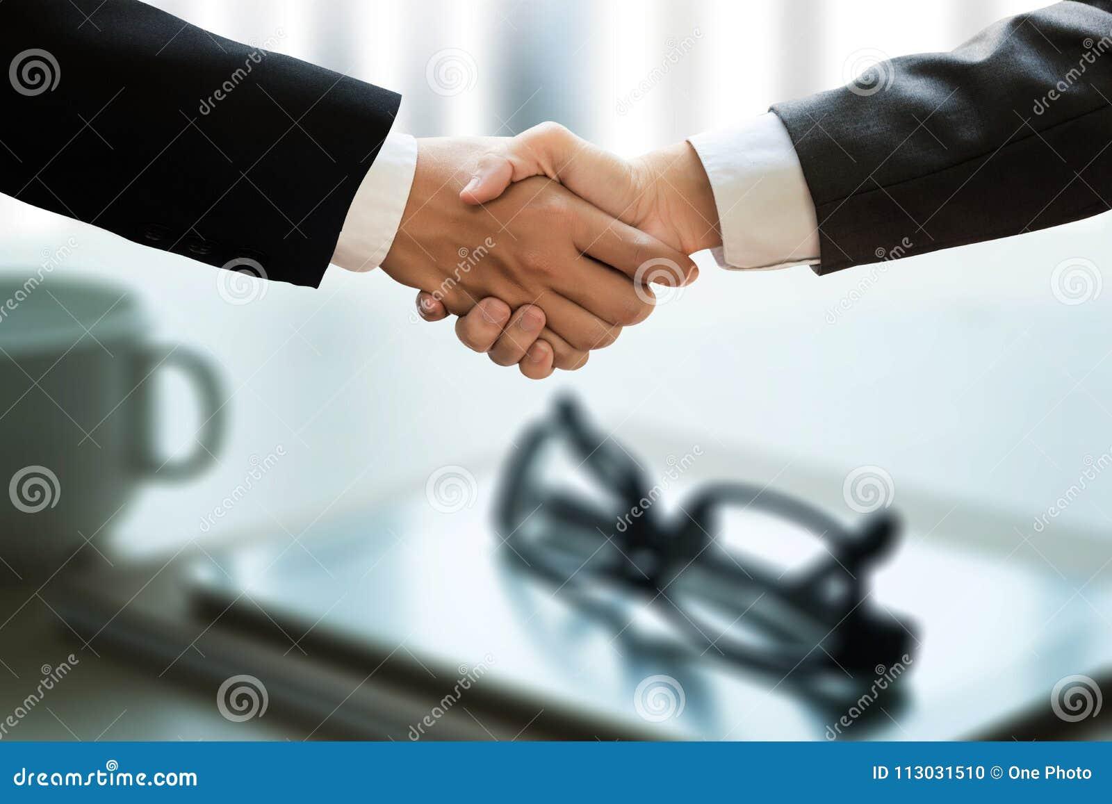 Apretón de manos acertado y hombres de negocios del negocio que se encuentran y