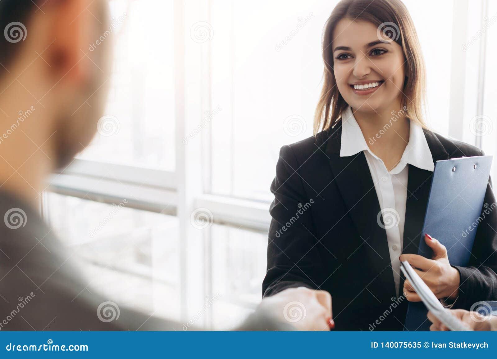 Apretón de manos atractivo sonriente de la empresaria con el hombre de negocios después de la charla agradable, buenas relaciones