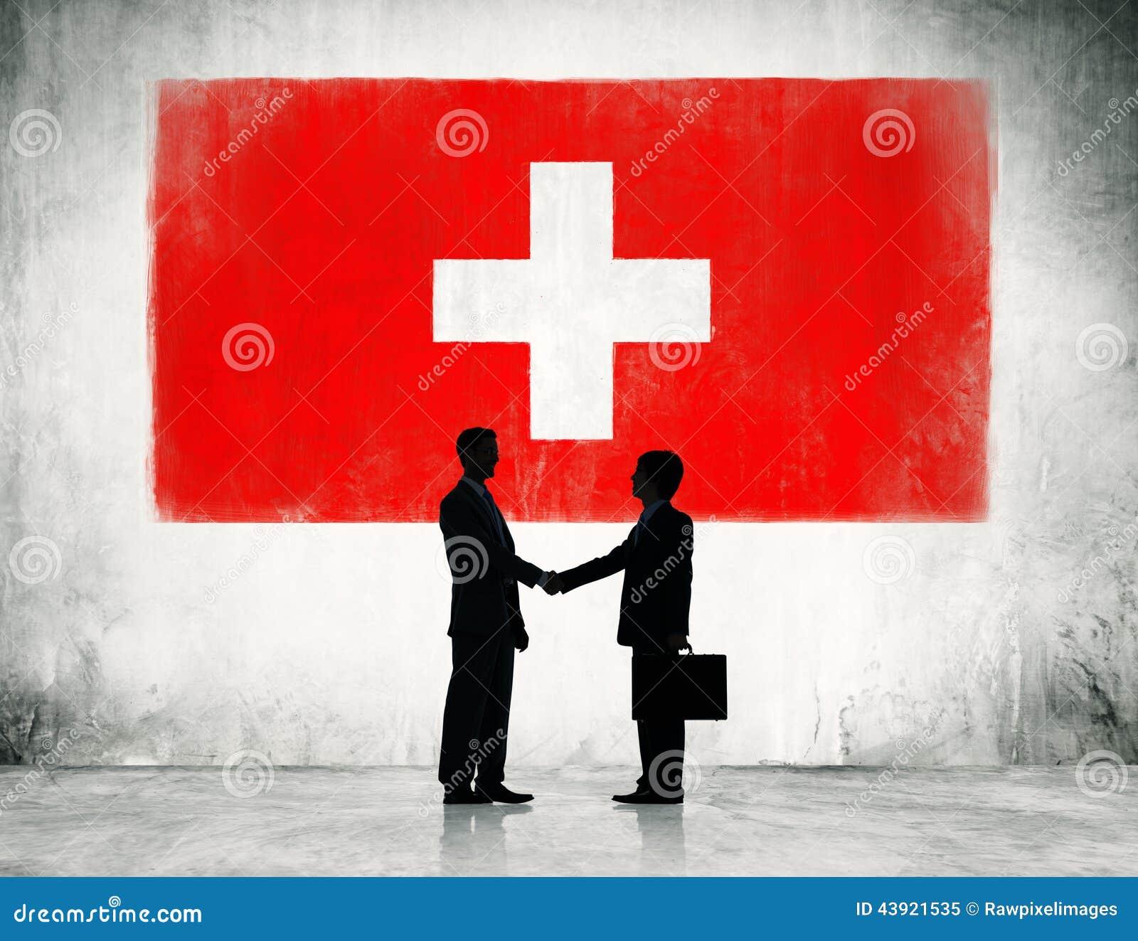 Apretón de manos de los hombres de negocios con la bandera de Suiza