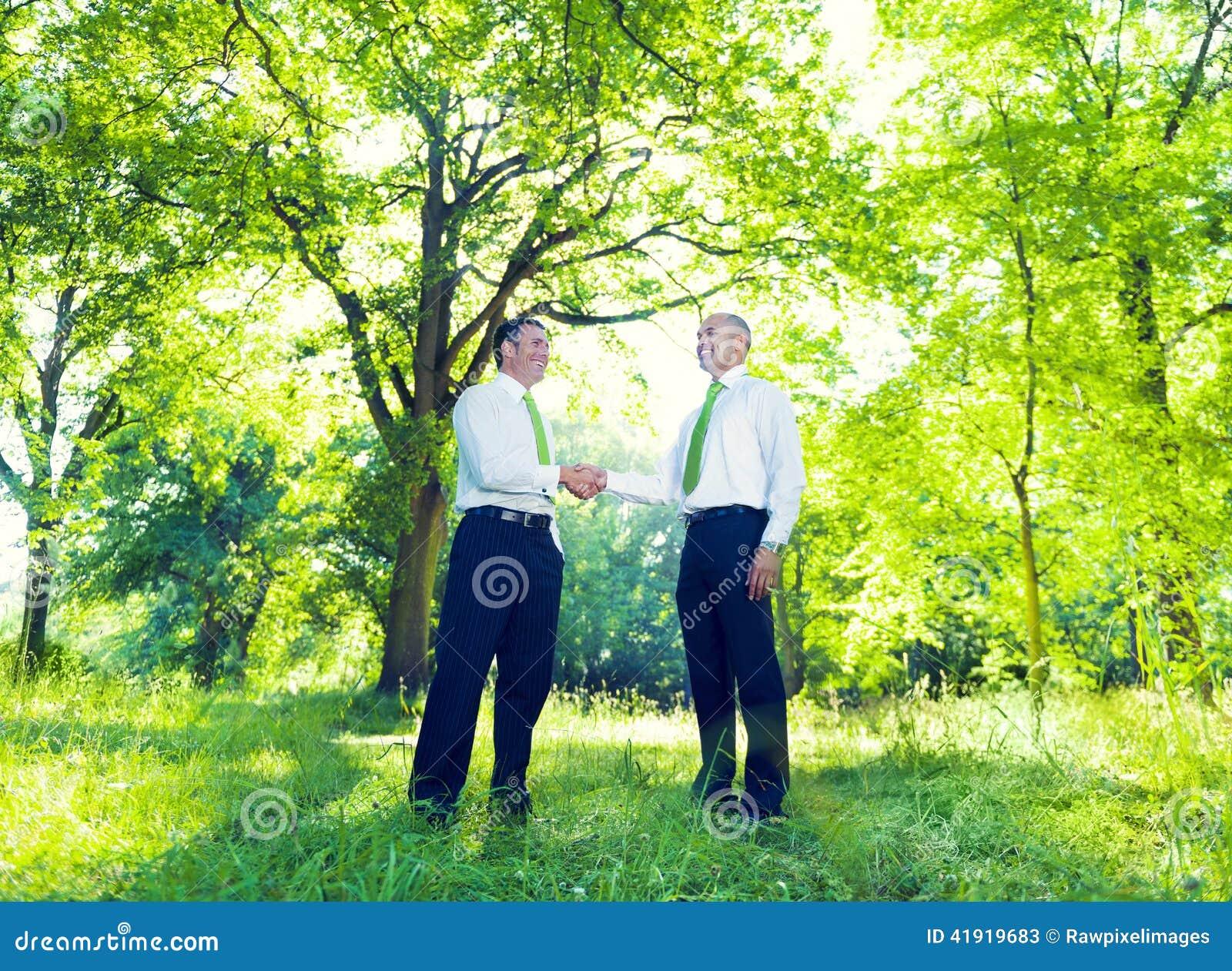 Apretón de manos de los hombres de negocios en jardín