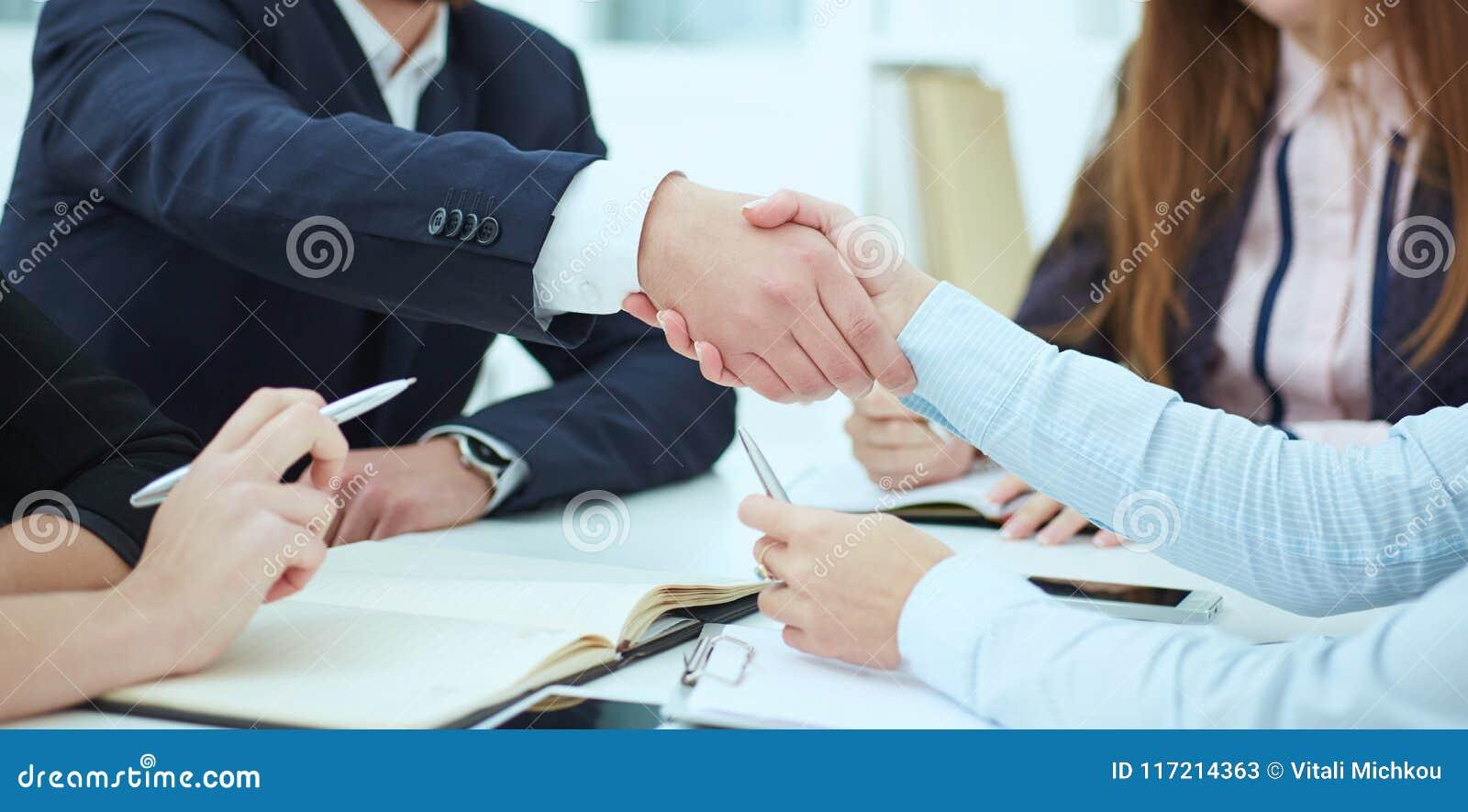 Apretón de manos masculino y femenino en oficina moderna Concepto serio del negocio y de la sociedad Socios hechos trato, sellado