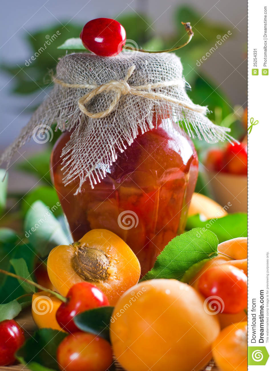 Apricot and sweet cherry jam in jar and fresh fruits with leaves.