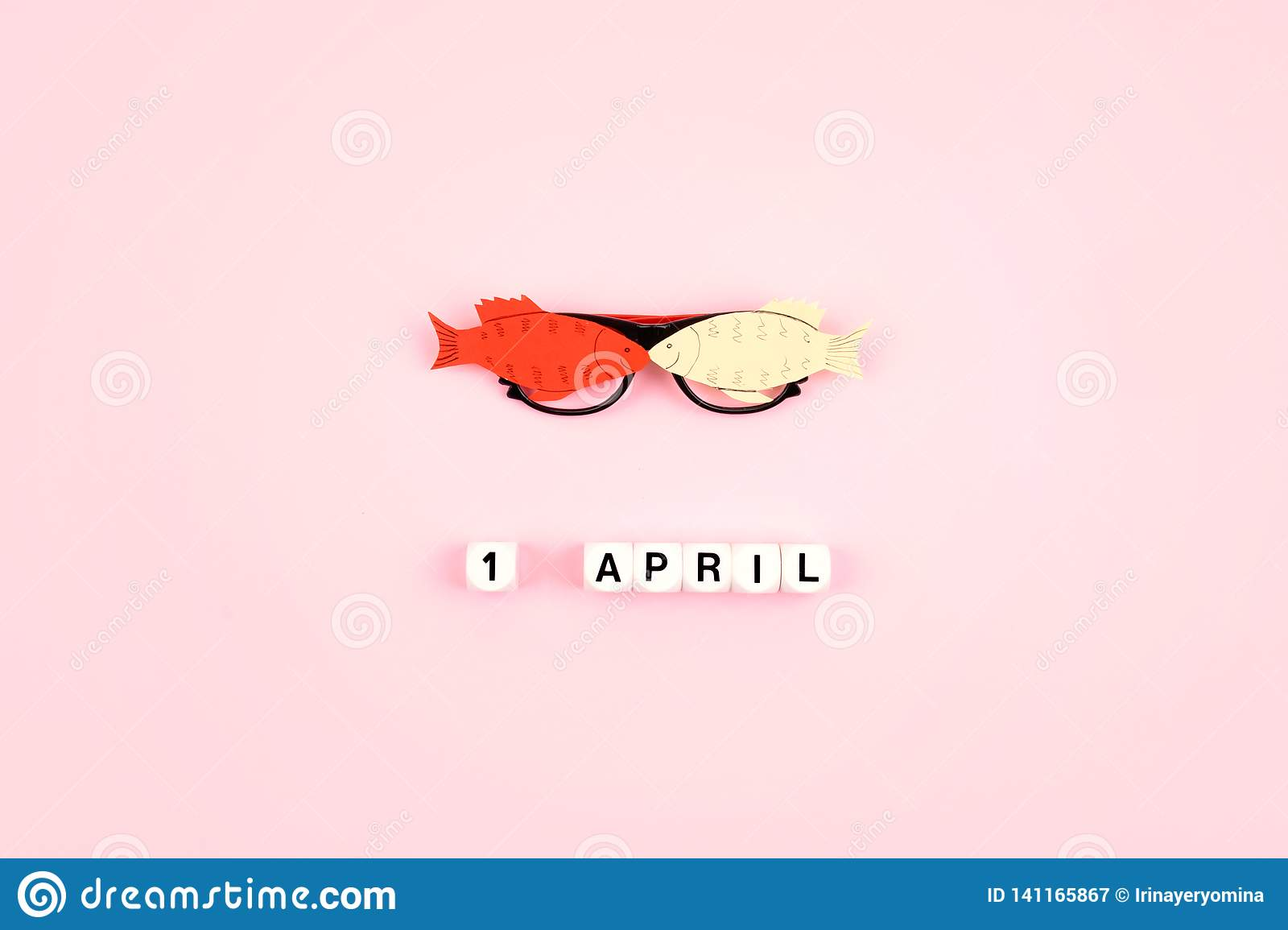 April Fools   Day celebration. Glasses with paper fish and text 1 April on pink background. All Fools   Day, humor, prank, joke