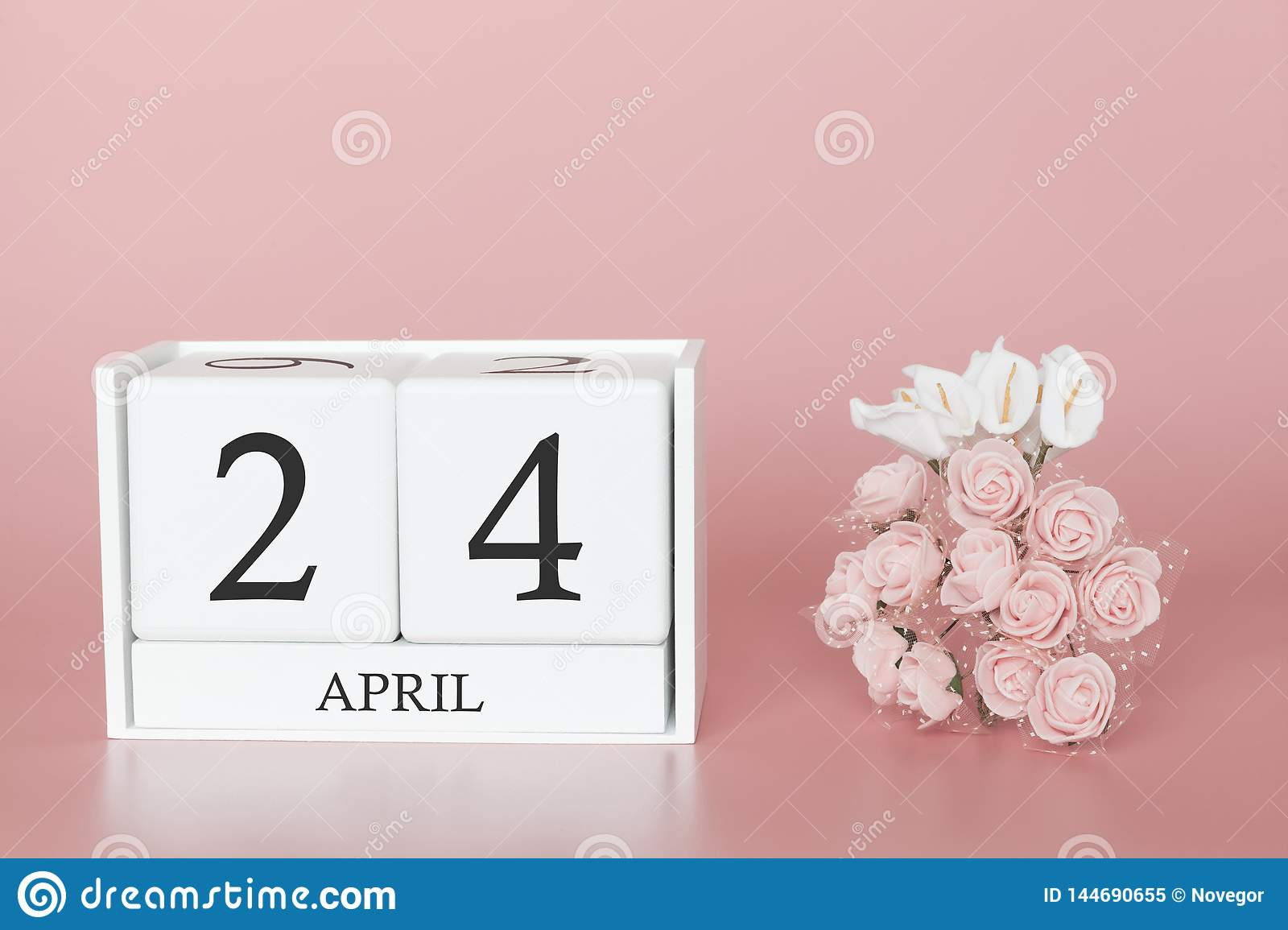 April 24th. Day 24 of month. Calendar cube on modern pink background, concept of bussines and an importent event