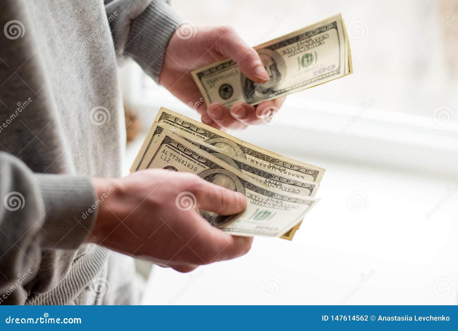 Aproveche las manos Beneficios, ahorros Pila de d?lares Hombre que cuenta el dinero E r