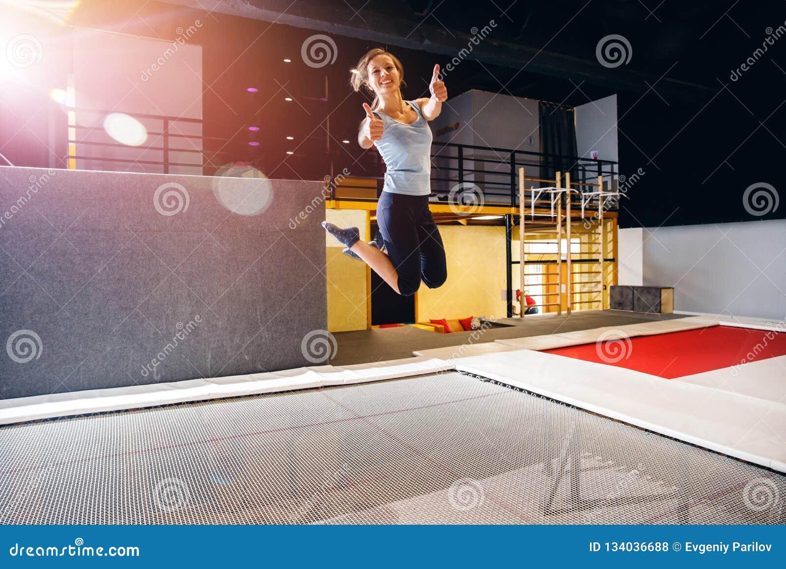 Aptidão do desportista da jovem mulher que salta no trampolim do clube