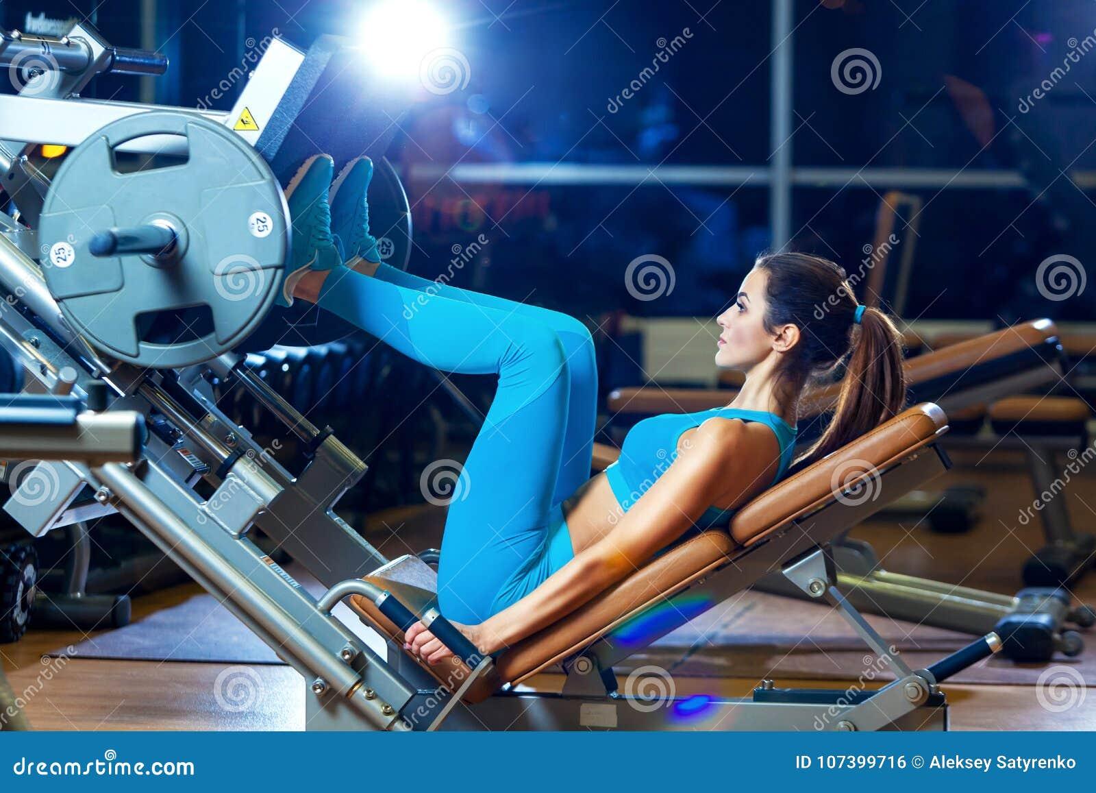 Aptidão, esporte, halterofilismo, exercício e conceito dos povos - jovem mulher que dobra os músculos na máquina da imprensa do p