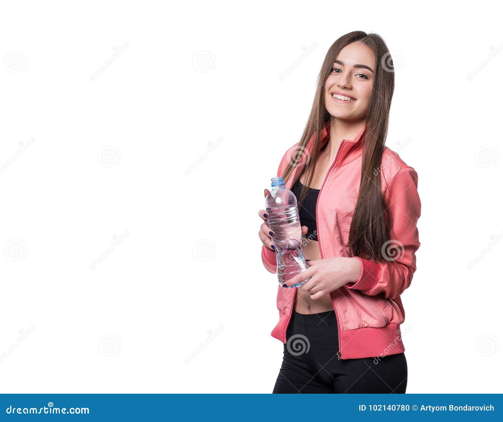 Aptidão-menina de sorriso nova no sportswear com a garrafa da água pura isolada no fundo branco Conceito saudável do estilo de vi