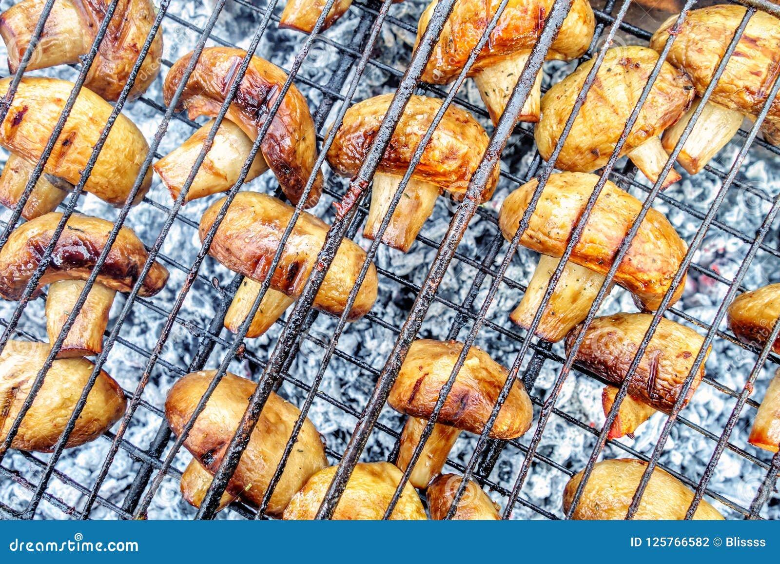 Aptitretande och smakligt organiskt halstrade/grillade/bakade/rökte champignonchampinjoner med den bruna skorpan som lagas mat på