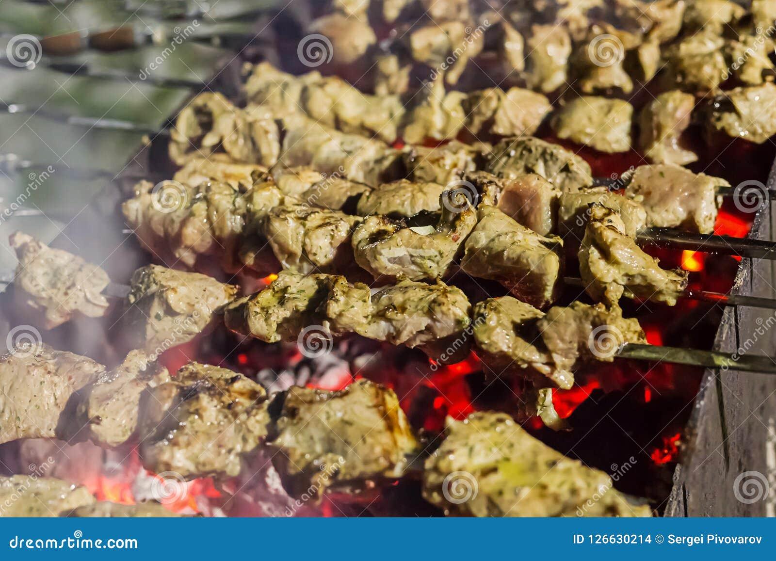 Aptitretande stycken av marinerat kött med kryddor stekt kebab över glödhet kolrad av griskötthöna på metallsteknålar