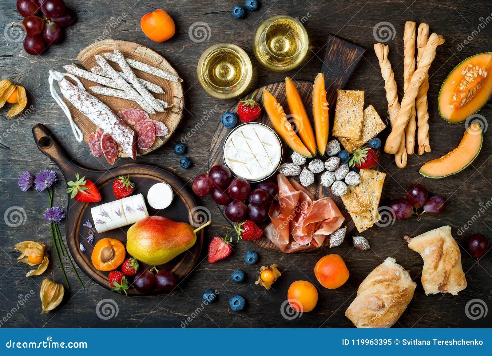 Aptitretare bordlägger med italienska antipastimellanmål och vin i exponeringsglas Ost- och charkuterivariation stiger ombord öve