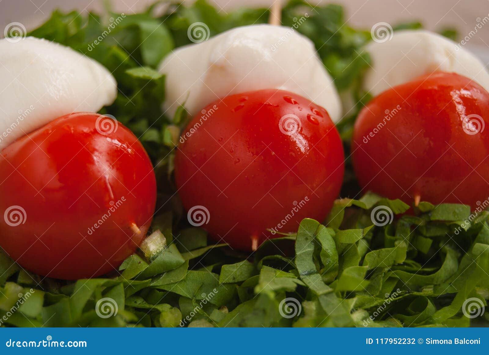 Aptitretare med tre steknålar med mozzarellaen och tomater