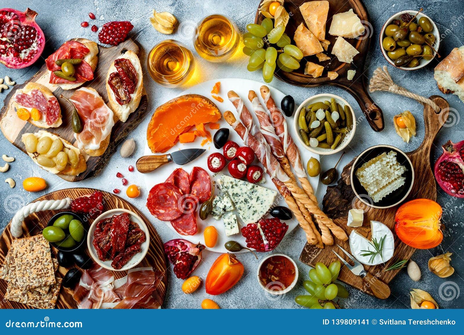 Aptitretaretabell med antipastimellanmål och vin i exponeringsglas Bruschetta eller autentiska traditionella spanska tapas uppsät