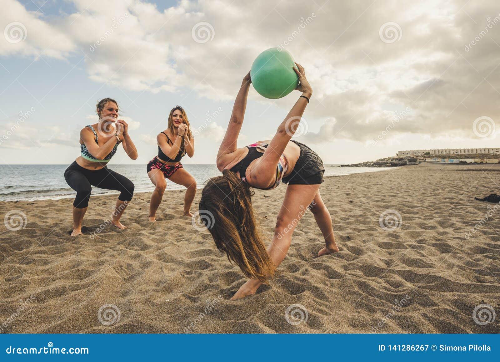 Aptitud, deporte, yoga y concepto sano de la forma de vida - grupo de personas que hace que los pilates presentan en la playa el