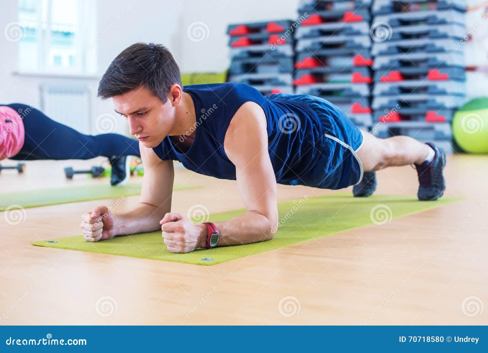 Aptitud que entrena al hombre deportivo atlético que hace ejercicio del tablón en gimnasio o a la clase de la yoga que ejercita e