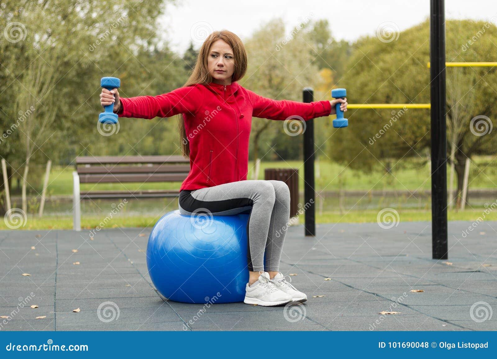 Aptitud, sana, aeróbicos, entrenamiento, mujer joven sonriente que hace ejercicio con la bola de los pilates en el patio del entr
