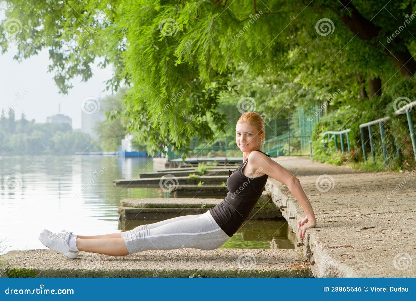 La mujer joven que hace la prensa sube en ejercicio urbano de la aptitud e88e5540283