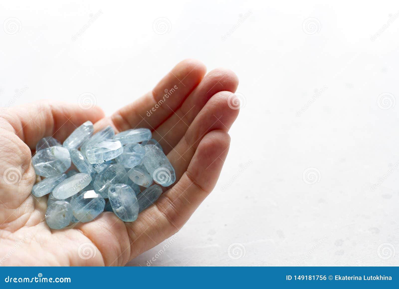 Aquamariner Stein liegt in der Hand Naturstein-Aquamarin auf einem wei?en Hintergrund Weibliche Hand kopieren Sie Platz f?r Ihren