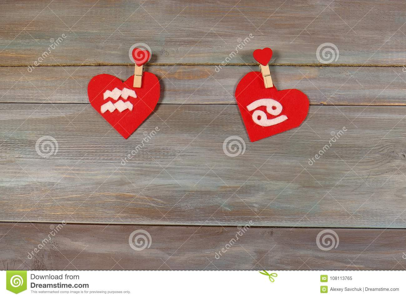 Aquarius and cancer. signs of the zodiac and heart. wooden backg