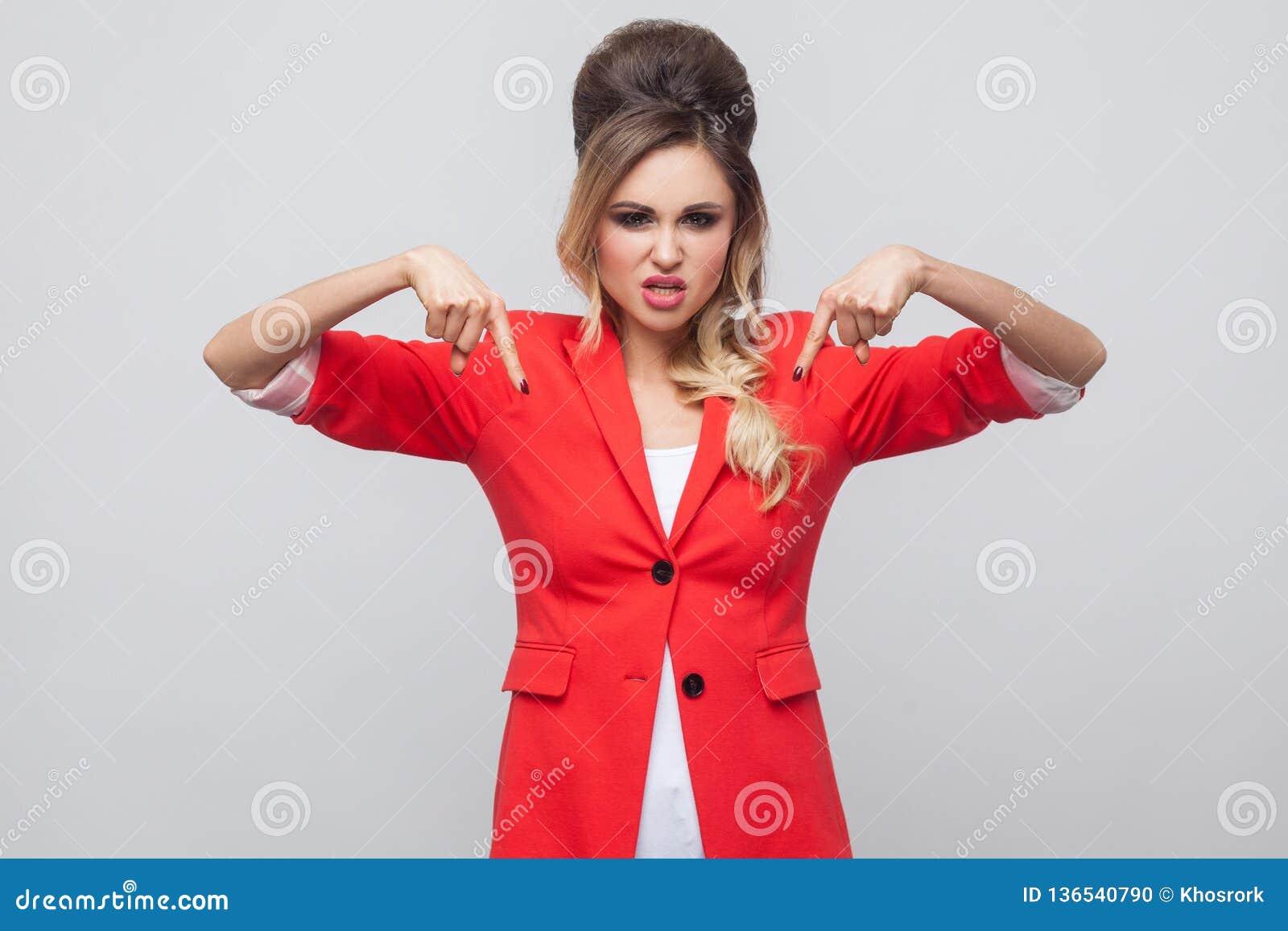 Aqui e agora Senhora bonita séria do negócio com penteado e composição no blazer extravagante vermelho, estar, olhando a câmera e