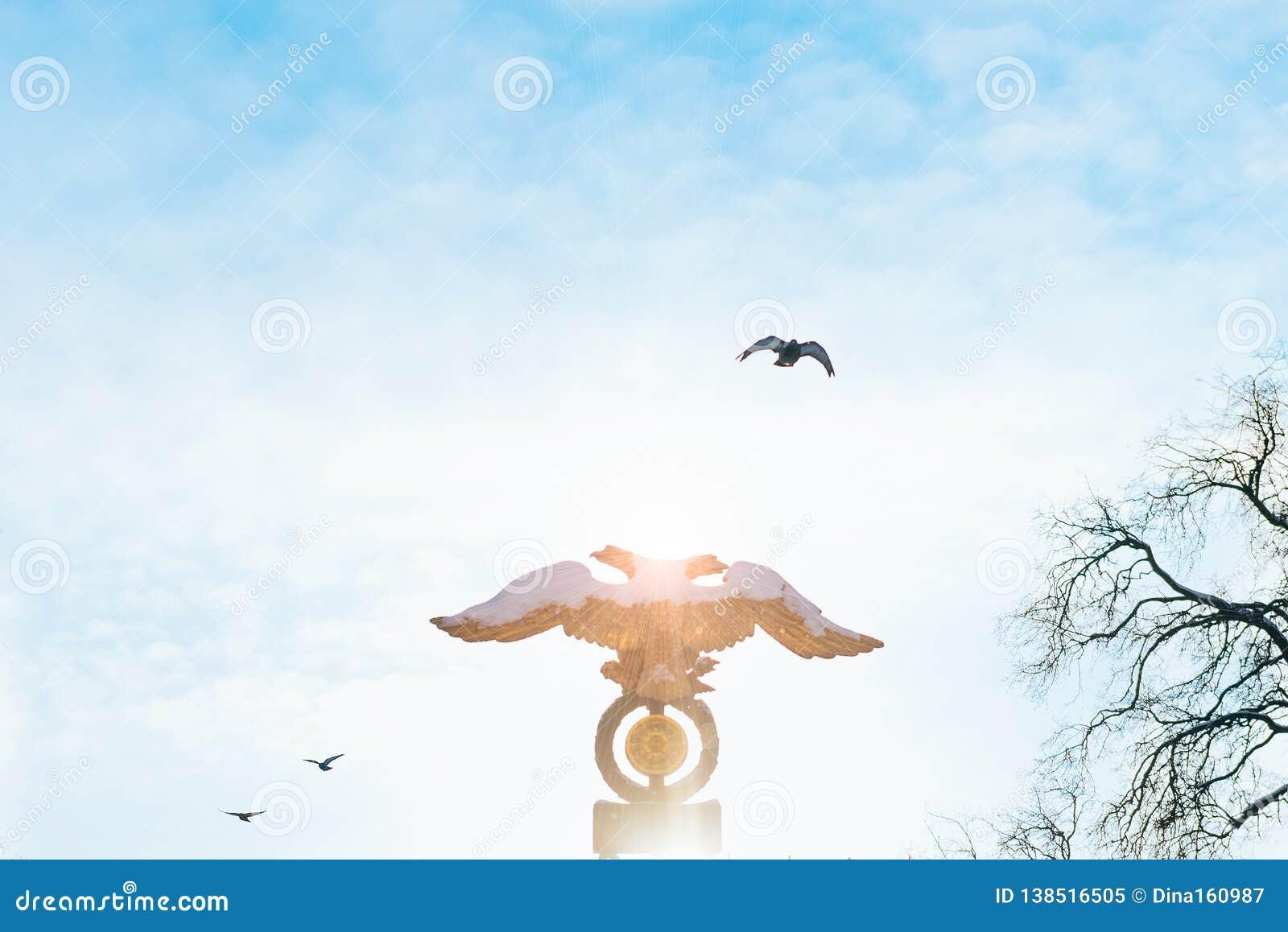 Aquila a due punte sul fondo del cielo ad alba con gli uccelli sui precedenti Emblema russo, doppia aquila intestata dorata