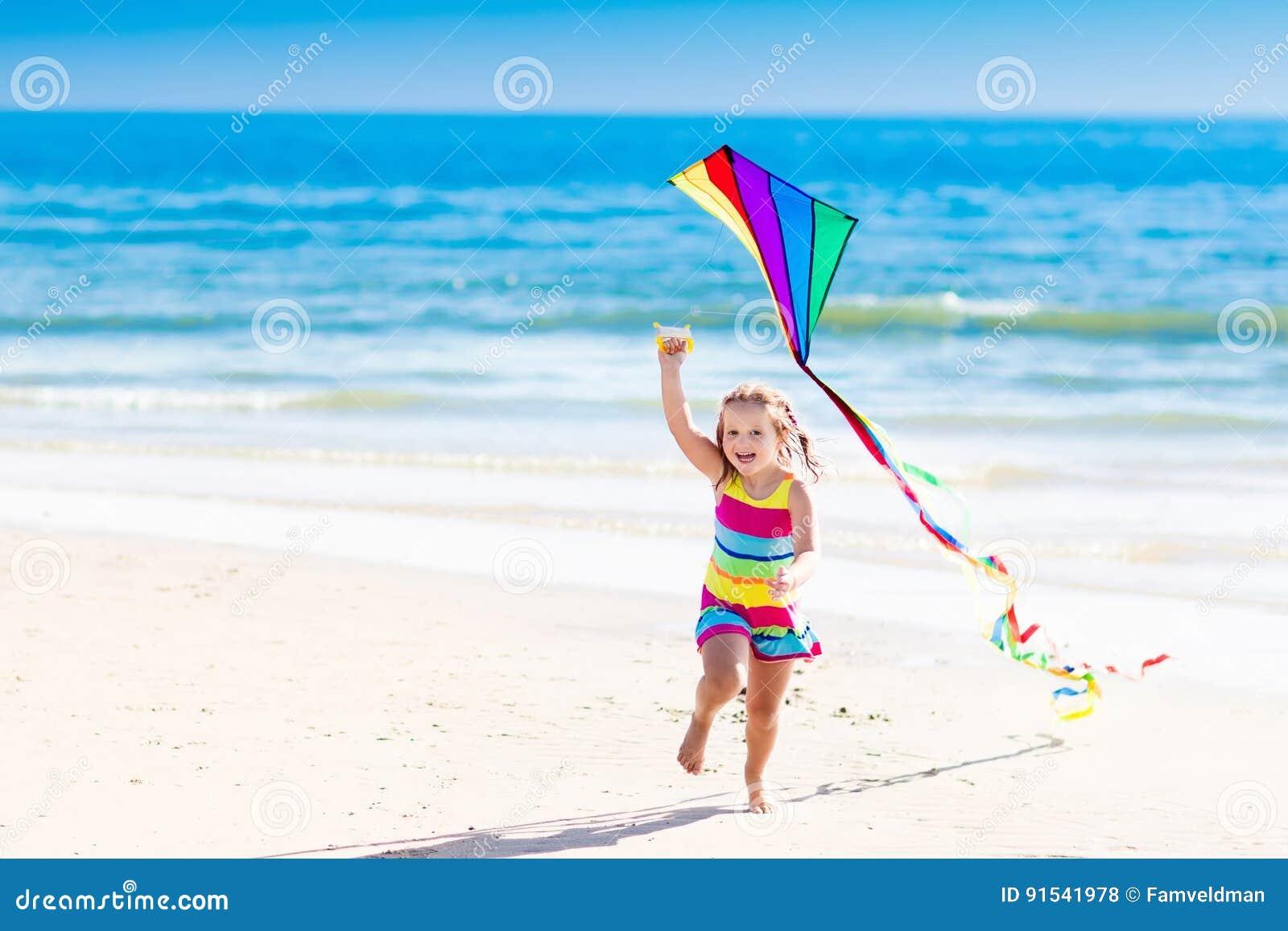 Aquilone di volo del bambino sulla spiaggia tropicale