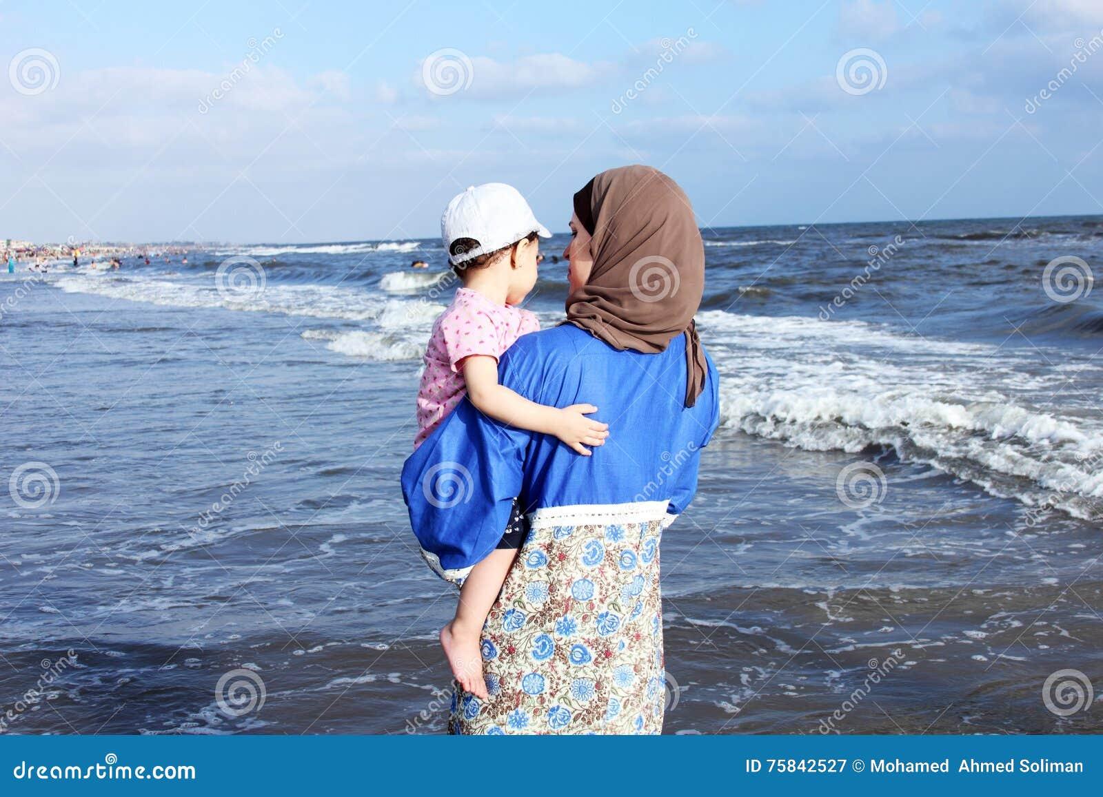 Arab egyptian muslim mother holding her baby girl on beach in egypt