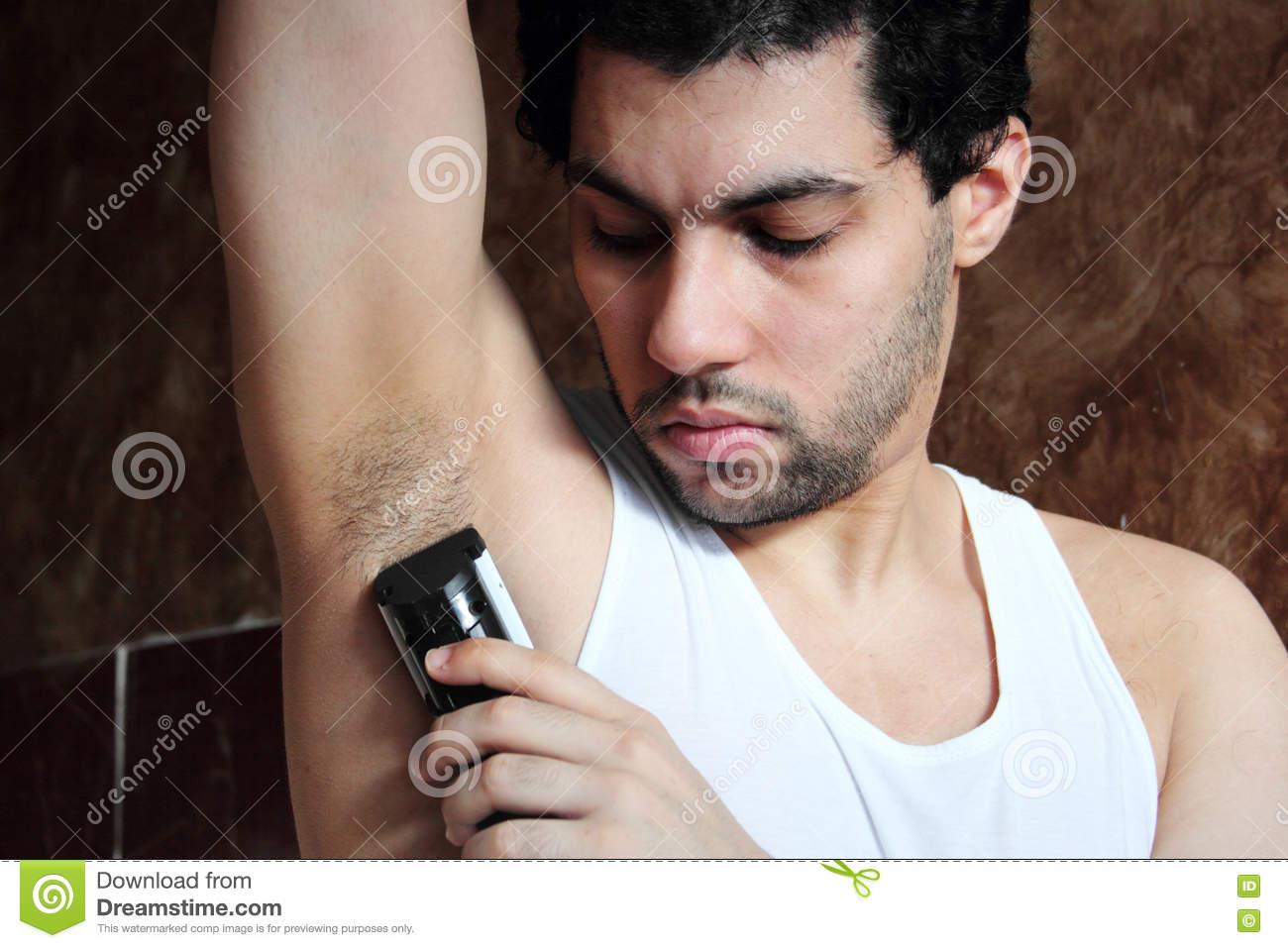 Arab Young Man Shaving Armpit Hair With Hair Clipper Stock