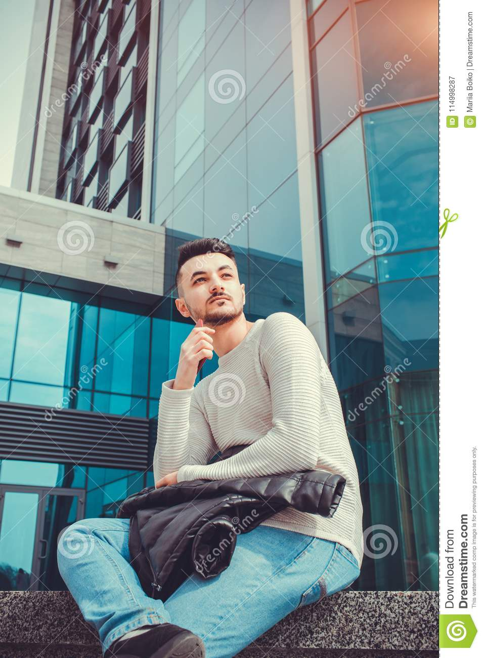 Arabian student waiting for a call outside. Man chilling out in front of modern building after classes