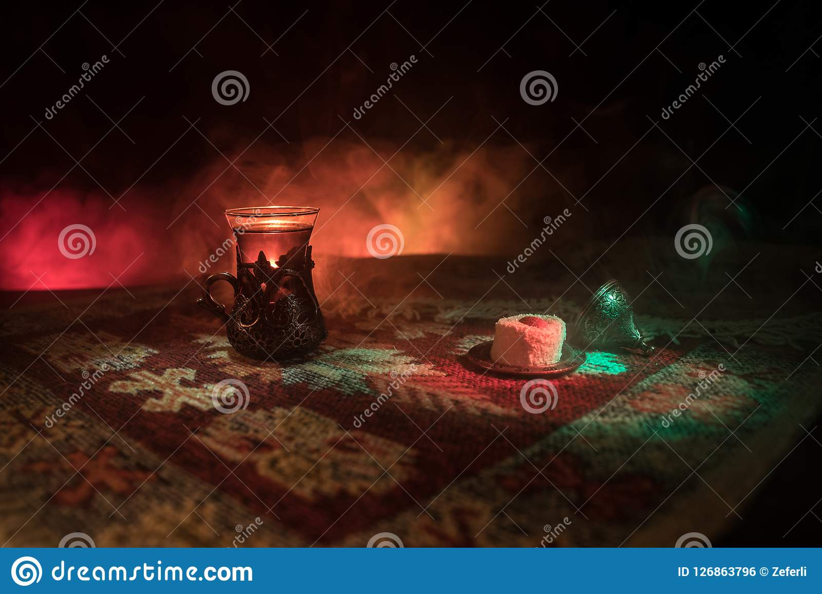 Arabian tea in glass with eastern snacks on a carpet on dark background with lights and smoke. Eastern tea concept. Empty space. Selective focus Royalty Free Stock Image