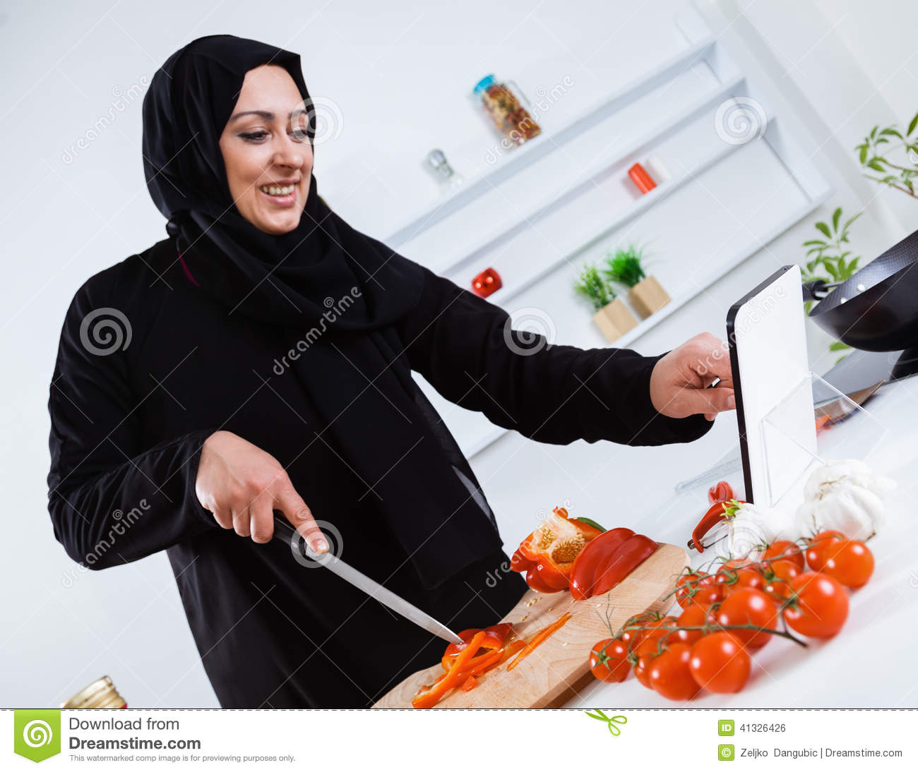 Women Kitchen: Arabian Woman Cooking In The Kitchen Stock Photo