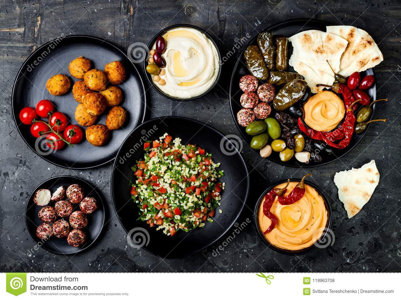 Arabic traditional cuisine. Middle Eastern meze platter with pita, olives, hummus, stuffed dolma, labneh cheese balls, falafel.