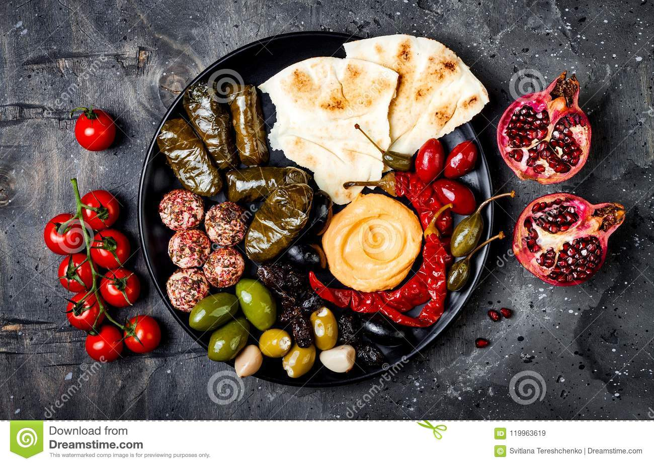 Arabic traditional cuisine. Middle Eastern meze platter with pita, olives, hummus, stuffed dolma, labneh cheese balls in spices.