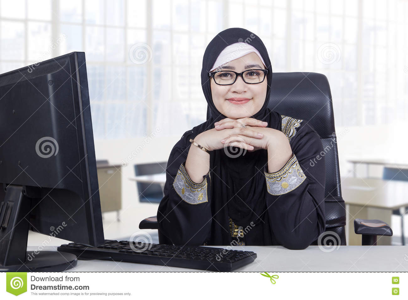Arabic woman with headscarf smiling in office