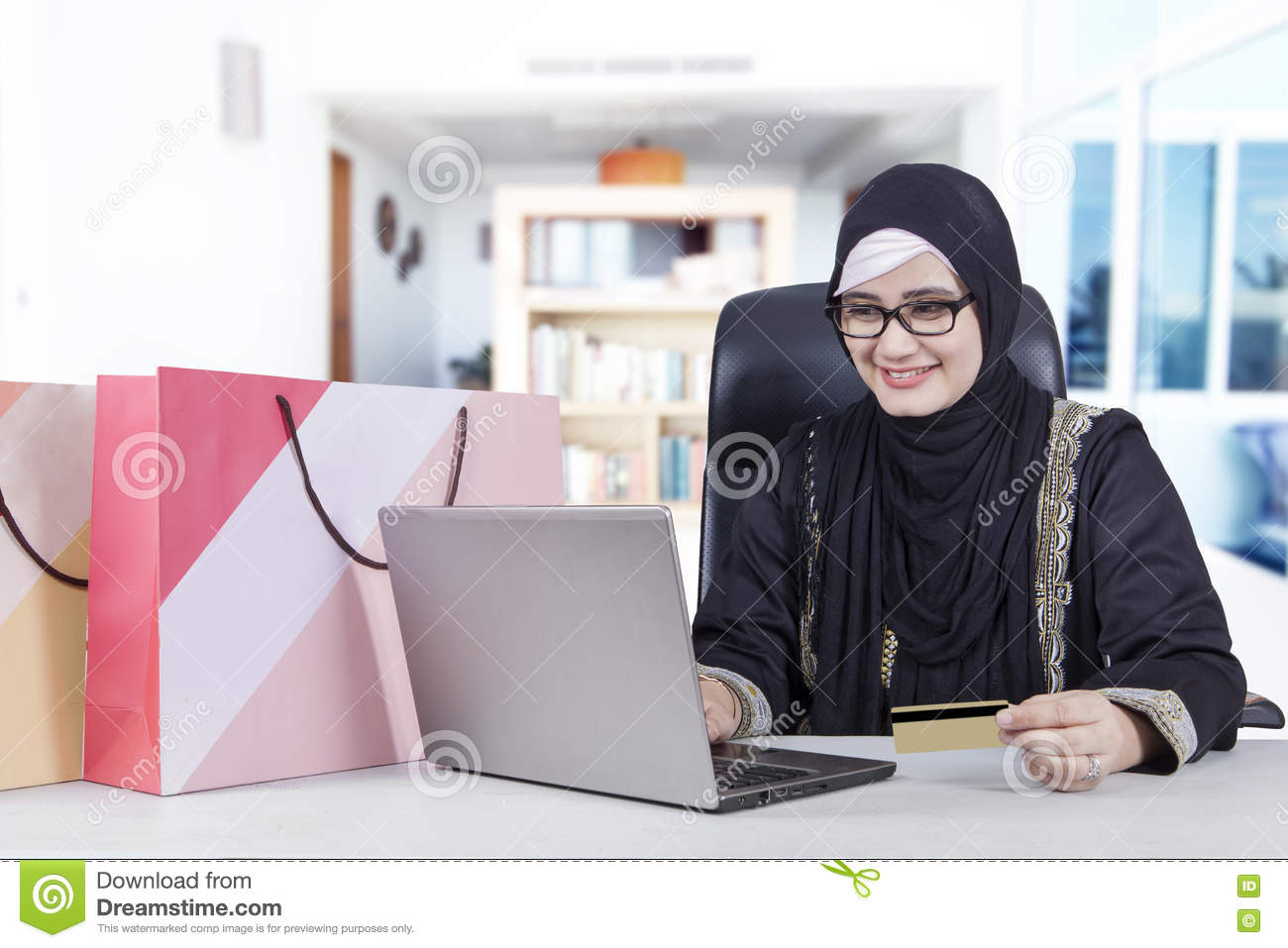 Arabic woman with notebook and credit card