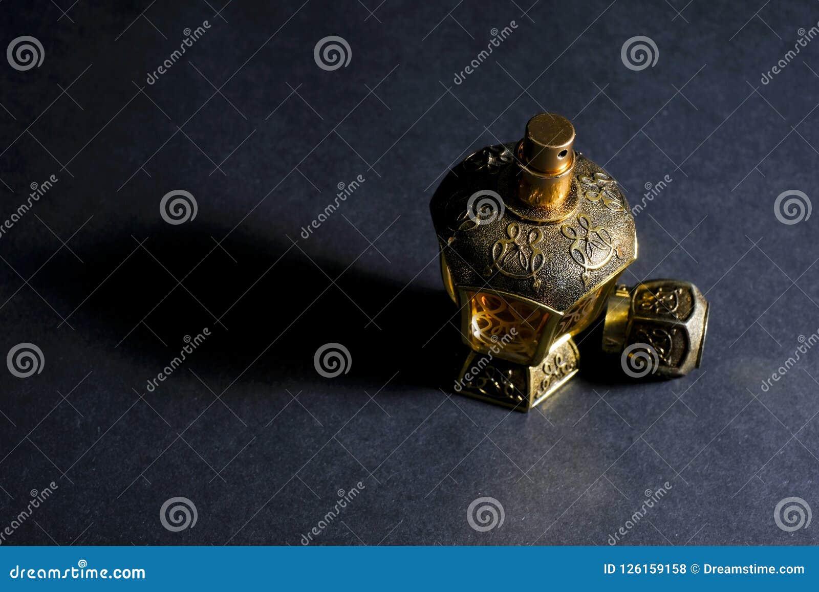 Arabisch die parfum in een fles, op zwarte achtergrond, in laag l wordt geïsoleerd
