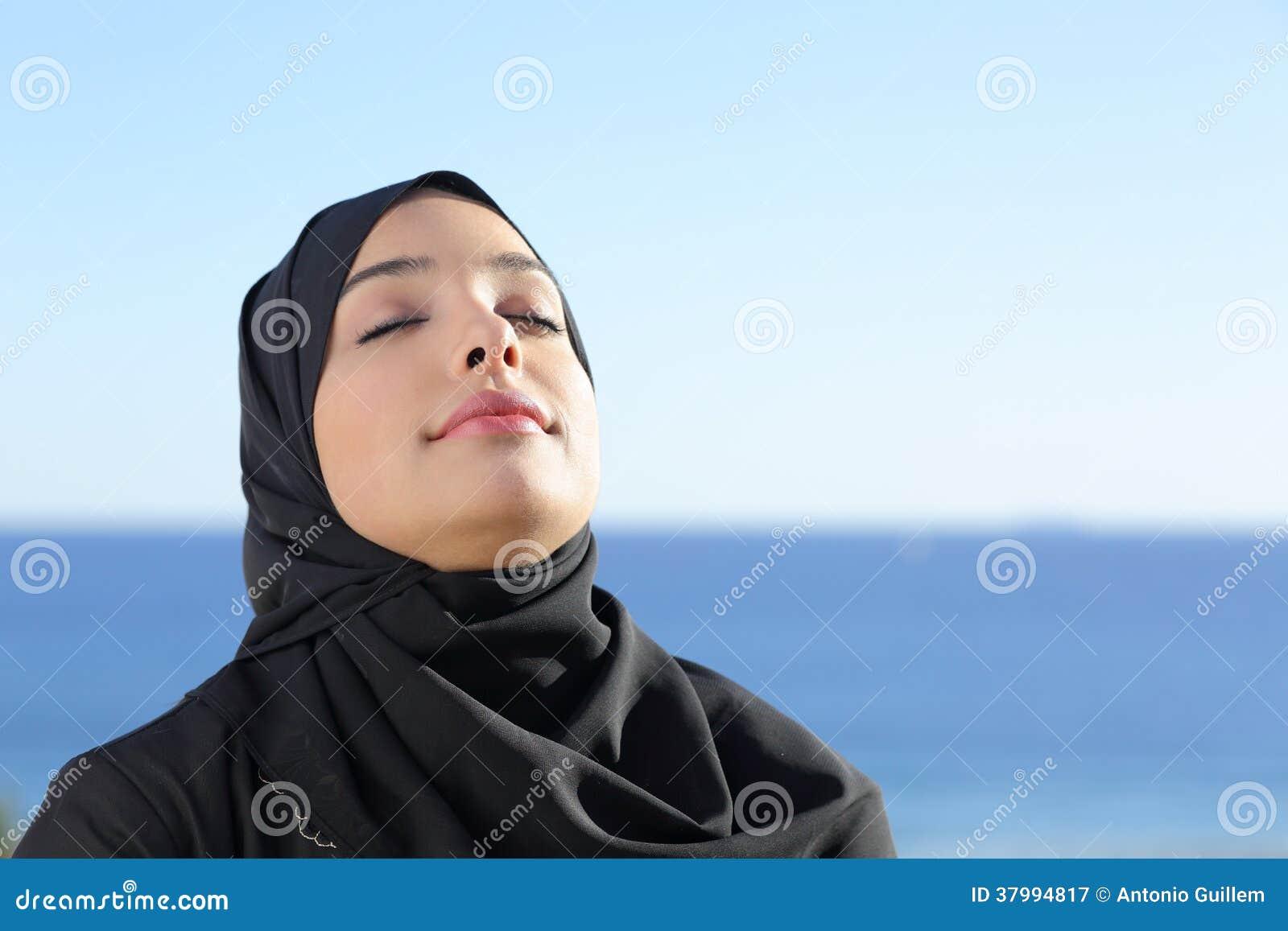 Arabische saudische Frau, die tiefe Frischluft im Strand atmet
